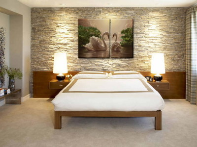 a stone wall behind the bed is quite a dramatic backdrop for this master bedroom suite.vintage lamps and modern furniture make an interesting combo.sofa in the sitting area is comfy and inviting.hand sewn sheets are an extra plus.